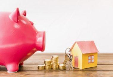 Encima da mesa: uma casa em miniatura, torres de moedas, um molho de chaves e um cofre de porquinho.