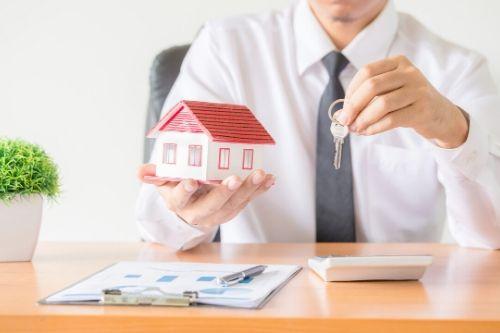 Homem segurando uma casa em miniatura e uma chave. Sobre a mesa: papeis, uma caneta e uma calculadora.