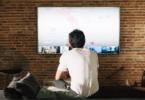 homem de costas sentado assistindo tv