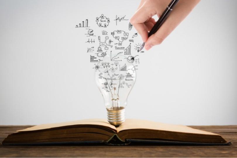 pessoa desenhando sob lampada e livro