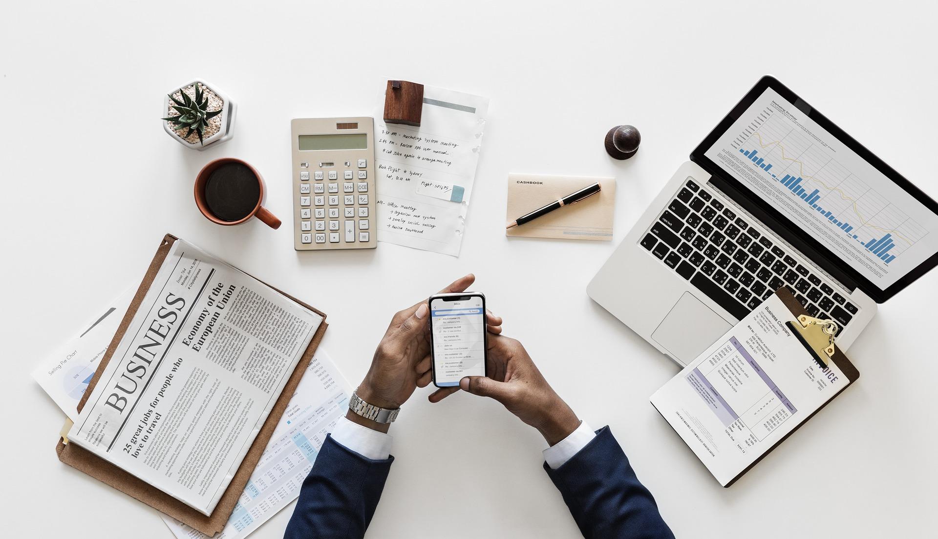 Mesa com notebook, celular, anotações, jornal e café
