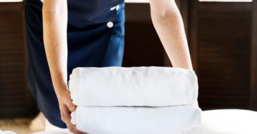 camareira organizando roupa de cama