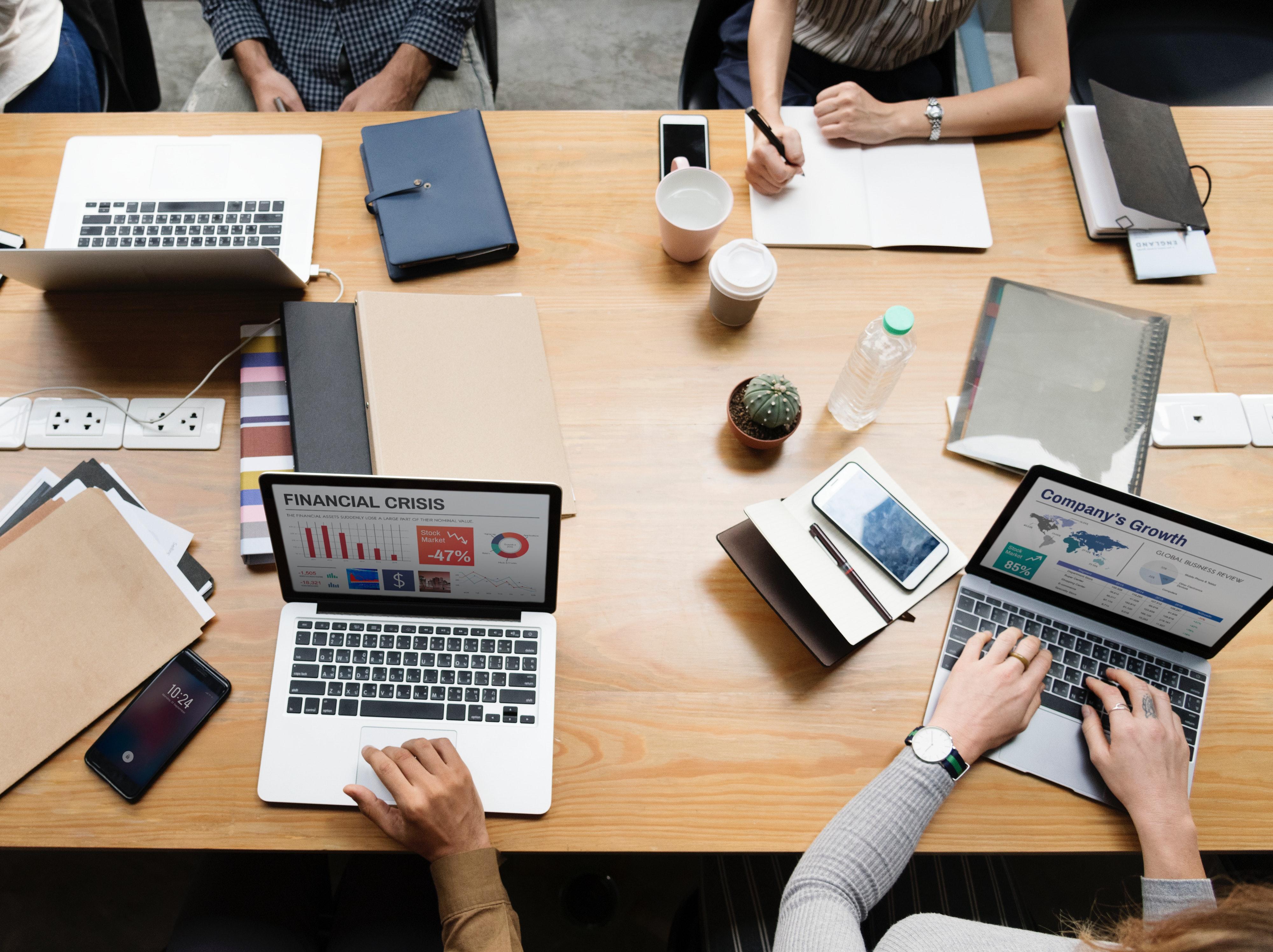 Pessoas discutindo em uma mesa com computadores