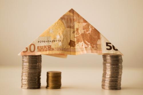 Moedas e uma nota de euro que formam uma casa