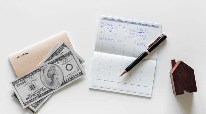Uma mesa cm anotações, dinheiro e uma pequena casa de madeira