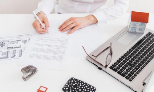 Mãos assinando contrato sobre uma mesa com notebooks, materiais de escritória e uma maquete de casa