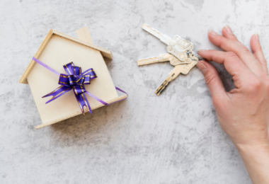 Mini casa com laço de presente e uma mão segurando chaves ao lado