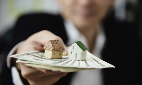 Um homem segurando notas de dinheiro e duas casinhas