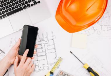 Mão digitando em um IPhone, notebook, plantas e um capacete de engenheiro civil sobre a mesa