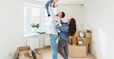 família composta por pai, mãe e filho. Estão em um ambiente com caixas de mudança e brincam de levantar a criança