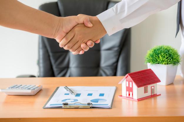 Duas pessoas apertando as mãos em frente a uma mesa com uma calculadora, maquete de casa e prancheta com gráficos.
