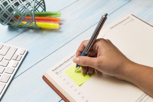 Pessoa fazendo anotações na agenda
