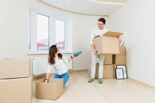 Homem e mulher abrindo caixas de mudança