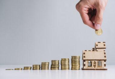 Mão colocando moedas em uma mini casa