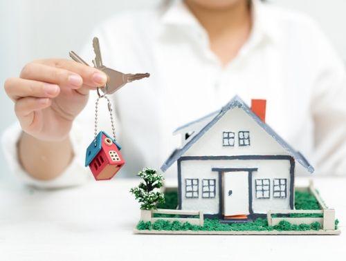 Agente imobiliária segurado chaves e com modelo de casa