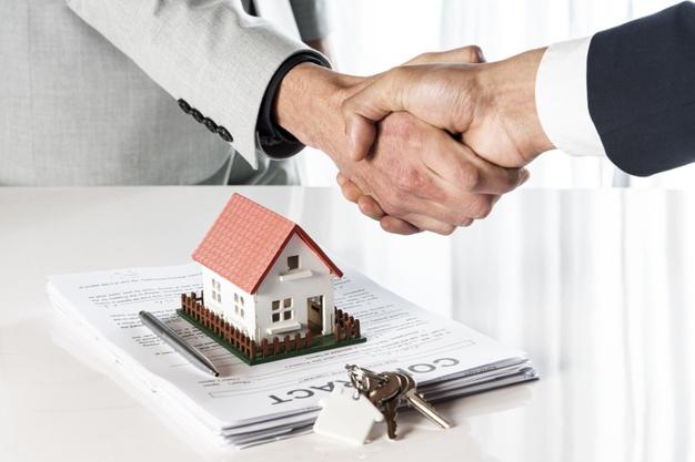 Duas pessoas apertando as mãos sobre uma mesa com um contrato, chaves e uma casa em miniatura.