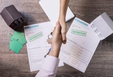 Duas pessoas apertando as mãos e fechando um contrato de venda de imóveis