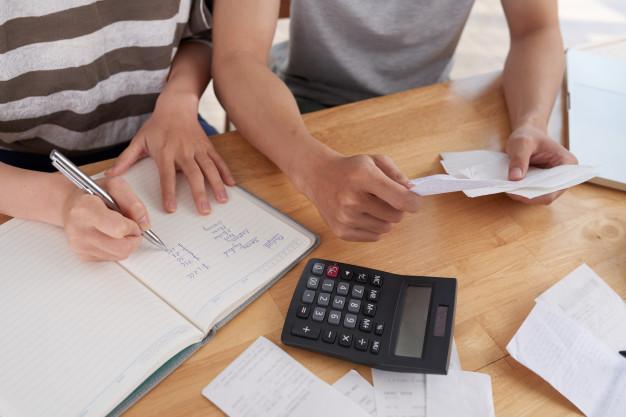 Uma pessoa escrevendo números em um caderno. Outra organizando notas. Sobre a mesa papeis e uma calculadora.