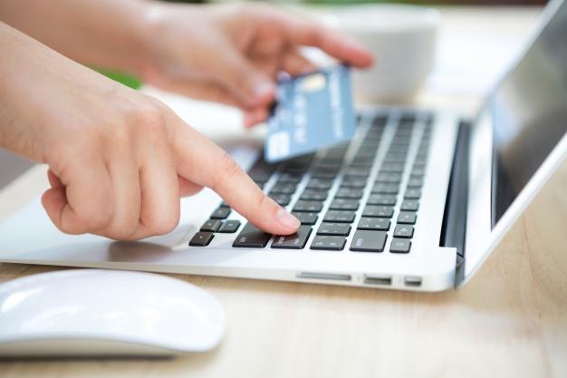 Pessoa segurando um cartão de crédito enquanto consulta algo em um notebook.