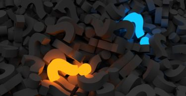 Vários pontos de interrogações pretos, azul luminoso e outro amarelo luminoso