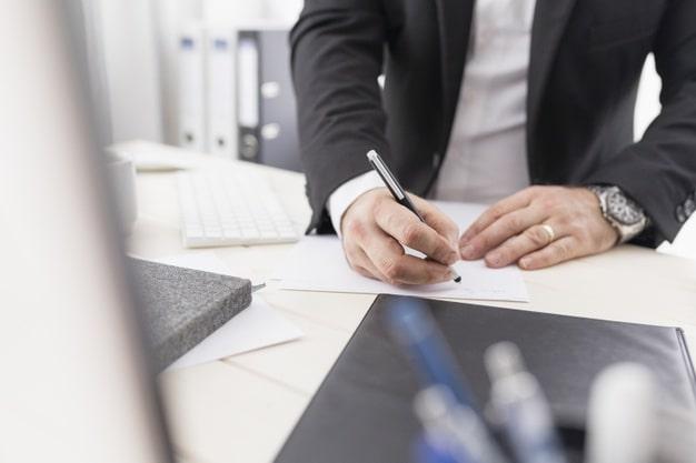 Homem assinando documentos.