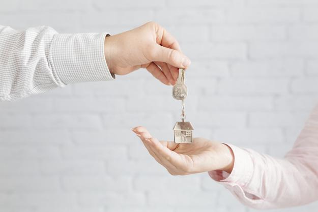 Uma mão entregando uma chave para outra mão