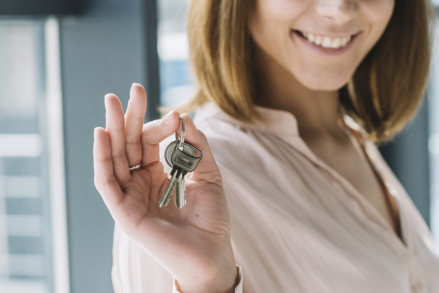 Mulher sorrindo segurando chaves