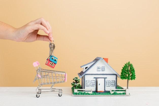 Uma casa e um carrinho de mercado em miniatura.