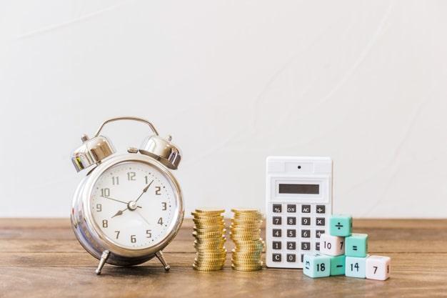 Em cima de uma mesa: um relógio despertador, torre de moedas, calculadora e dados empulhados com valores em porcentagens.