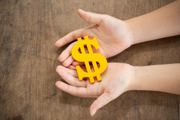 Mãos segurando um cifrão amarelo.