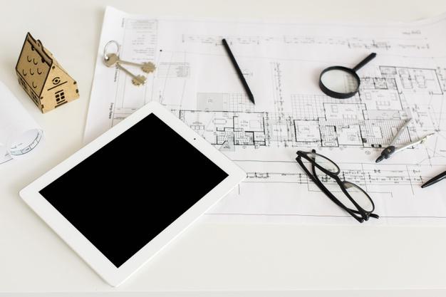 Sobre uma mesa um planta, uma casa em miniatura, um tablet, lupa, lápis, óculos e chaves.