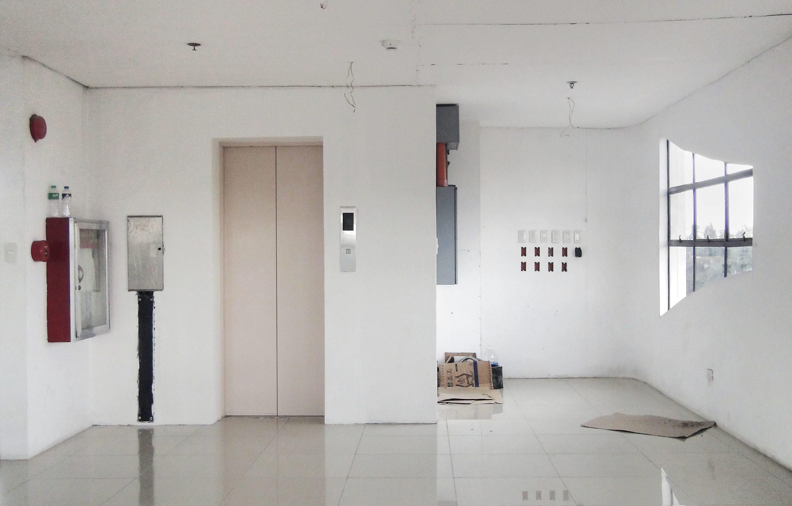 Imagem de um hall de prédio antigo e em reforma. É visível a porta de um elevador, janelas e mangueira de incêndio.