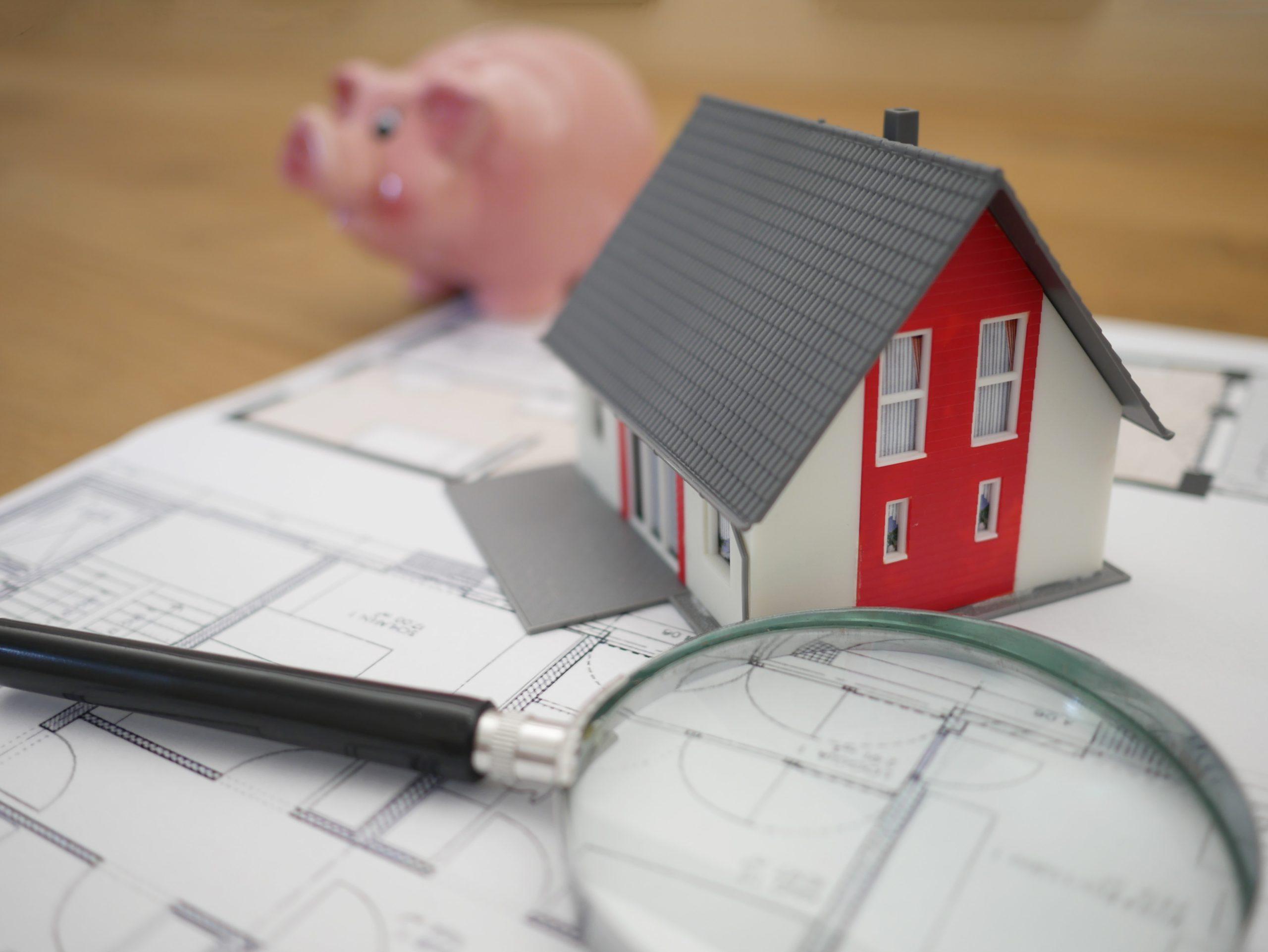 Sobre uma mesa um planta de casa, uma casa em miniatura, uma lupa e um cofre de porquinho.