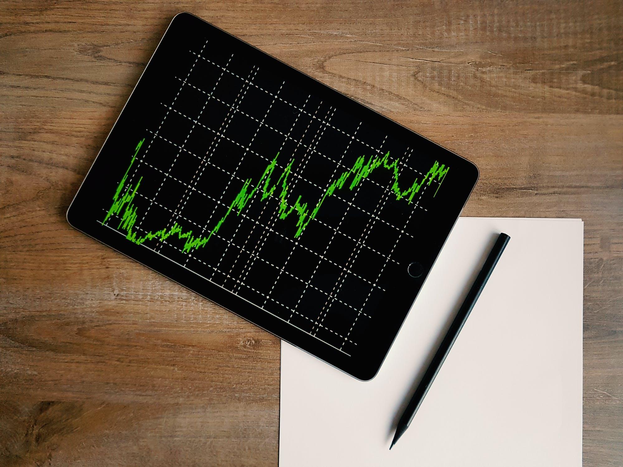 Sobre um mesa um papel, um lápis e um tablet com um gráfico linhas crescente.