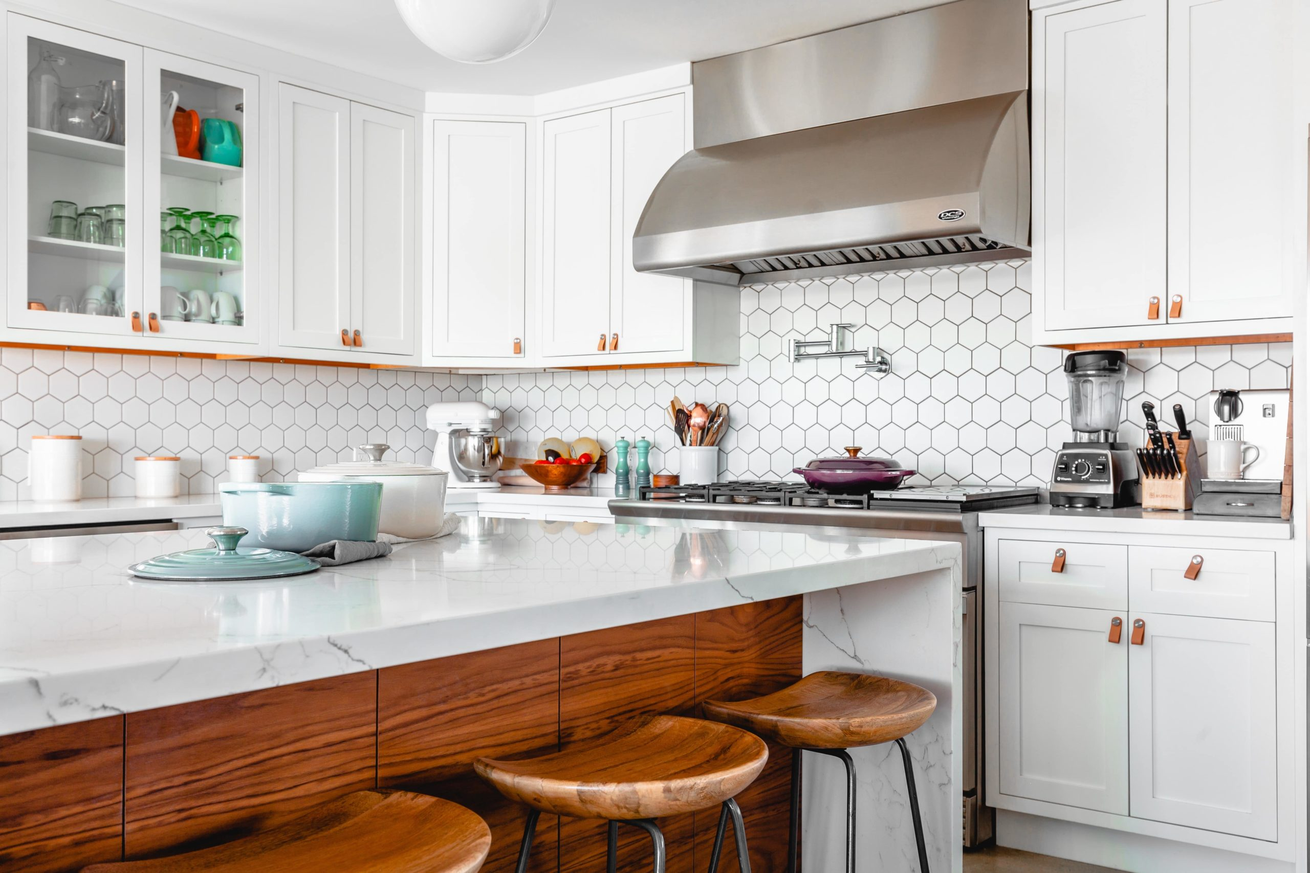 Imagem de uma cozinha branca com armários, fogão, ilha central, e 3 banquetas