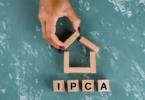 Mão colocando peças para forma um casa. Palavra IPCA sob a casa.