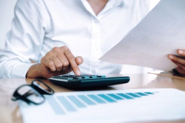 Mulher fazendo contas em uma calculadora